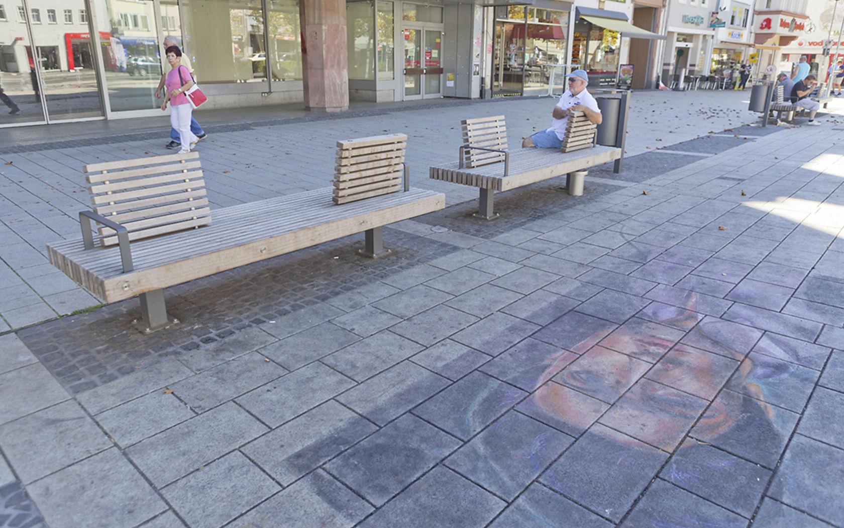 Der Platz in der Fußgängerzone mit Sitzmöglichkeiten aus Holz sieht mit den Verschmutzungen am Boden nicht mehr einladend aus.