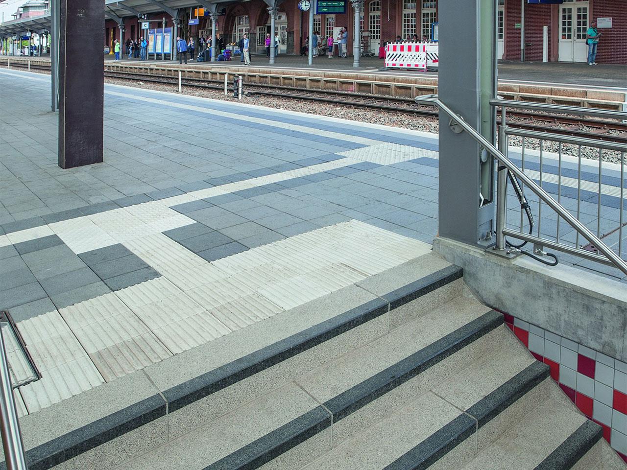 Kontraststreifen und Platten mit Profil am Bahnsteig.