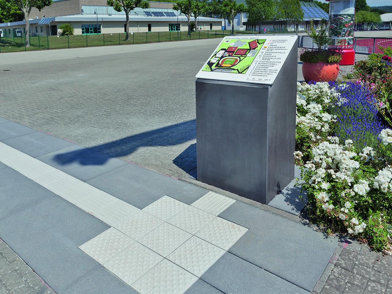 Noppen und Rillenplatten und Anzeigetafeln mit Blindenschrift für die barrierefreie Wegeführung im öffentlichen Raum.