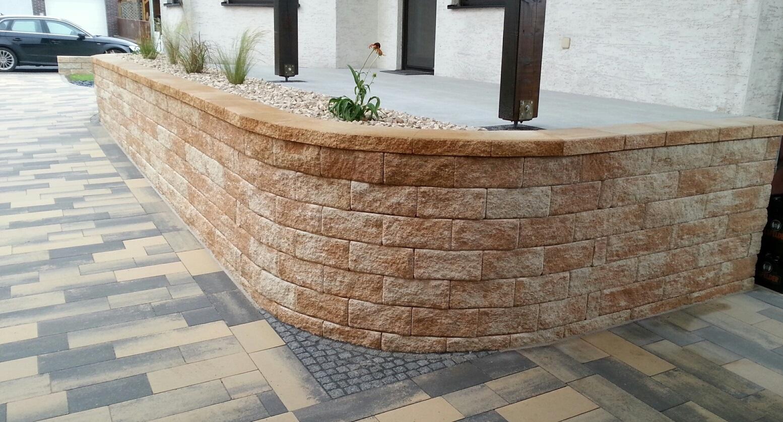 Die rustikale Mauer sichert die Terrasse ab, auf dem Weg liegt ein großformatiges Pflaster