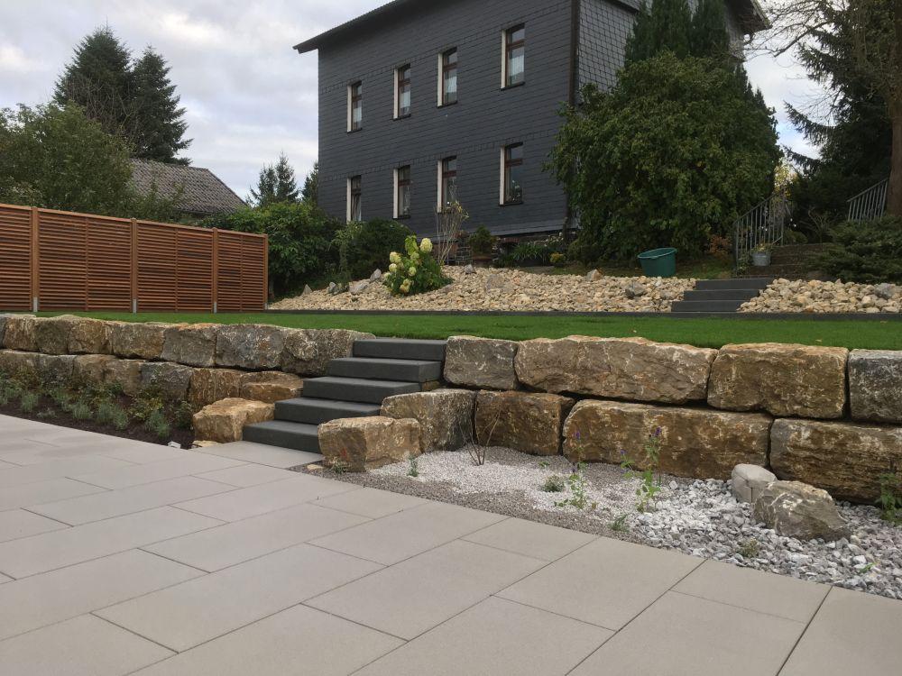 Terrasse mit beschichteten Betonplatten und Treppenanlage mit Blockstufen in Basalt