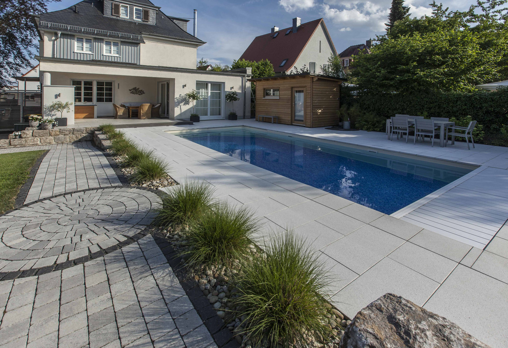 Gartengestaltung rund um den Pool mit beschichteten Betonplatten sowie ein Gehweg mit Pflastersteinen in rustikaler Optik