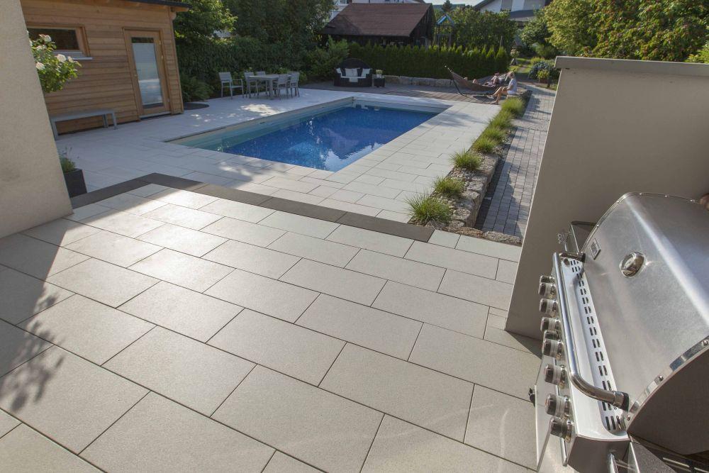 Terrasse mit beschichteten Betonplatten und optischer Trennung zum Garten