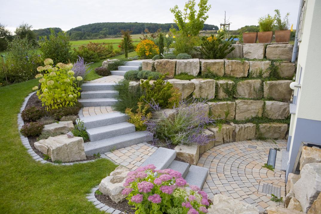 Hangabsicherung mit einer Treppenanlage aus Blockstufen und Natursteinmauer