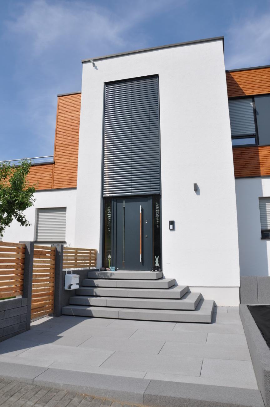 Moderner Eingangsbereich mit Platten und freitragenden Blockstufen