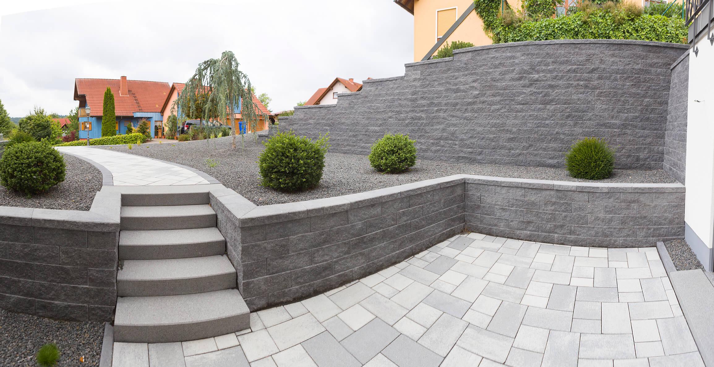 Terrasse mit Pflastersteinen und Mauer in Grau-Anthrazit